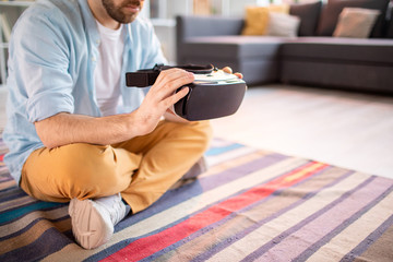 Casual man with crossed legs sitting on the floor of living-room with vr headset in hands