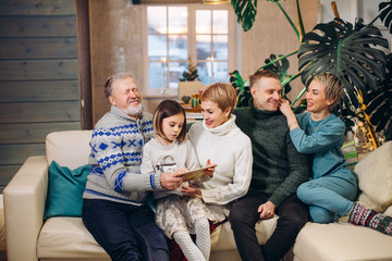 extended cheerful family enjoys leisure time indoors. stories from the past. large family having fun in the living room