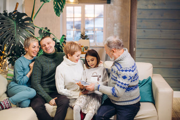 united large family watching photos while resting on the couch in the living room.free time , lifestyle. little girl teaching her grandfather to use tablet