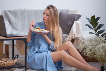 young woman sitting at home on the floor eating salad and watching a TV series or news on a laptop. fast life in a modern city.