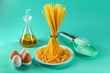 bunch of spaghetti standing upright on a bright colored background surrounded by chicken eggs, olive oil and cooking utensils. Horizontal.