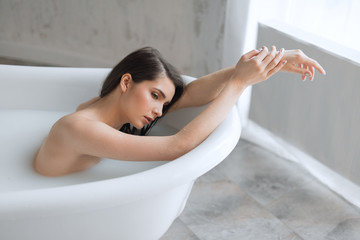 Attractive young woman with healthy white skin and brown hair, chilling in spa salon, taking milk bath, being totally relaxed and satisfied.