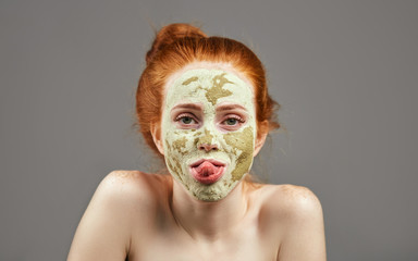 funny ginger girl with green mask showing her tongue. close up photo. studio shot.carzy girl sticking out her tongue