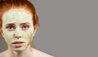 serios girl with clay mask. close up cropped photo. copy space . carbonated clay mask for face for young skin