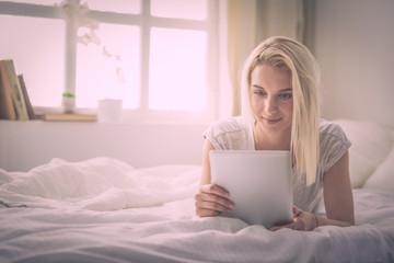 Girl holding digital tablet with blank screen and smiling at camera in bedroom