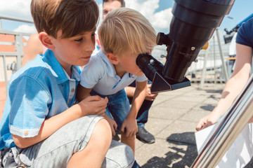 Young boy looking thru sun refractor in public star observatory