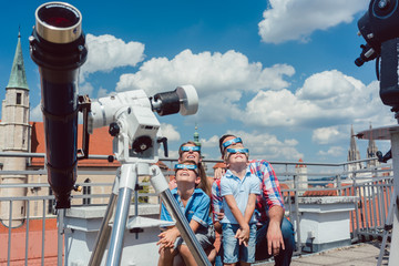 Family watching a solar eclipse in historic star observatory