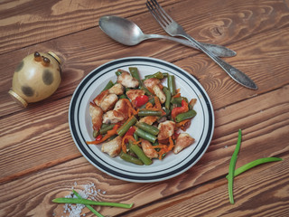 A plate with freshly prepared vegetables beans, wetter, pepper and onions, chicken pieces on a wooden background.