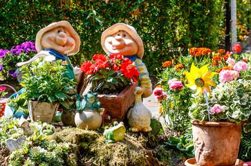 Landschaft mit zwei lustigen Gartenzwergen zwischen bunten Blumentöpfen in the Spreewald Biosphäre Reserve, Brandenburg, nahe Berlin Germany