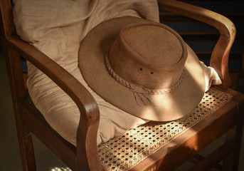 Brown suede leather cowboy hat laid on vintage wooden armchair with window  light on part of a30de9d4a73e