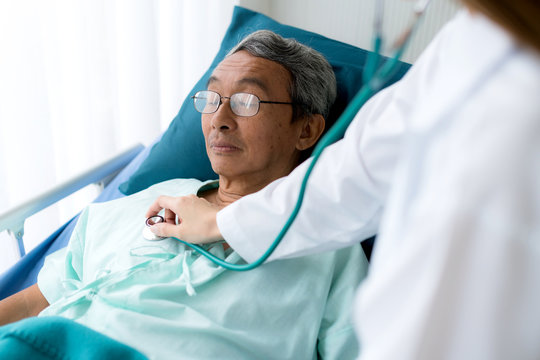 doctor with clipboard checking up and discussing with old asian man patient lay on bed in hospital with care and happiness