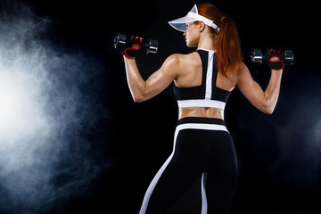 Sporty fit woman, athlete with dumbbells make fitness exercises on black background.