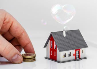 dream of buying or owning a house - heart spaped soap bubble over model house