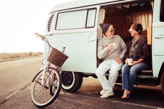 Adult aged caucasian happy couple sit down out of a vintage van drinking a tea and enjoying the outdoor leisure activity during travel vacation - bike parked near the vehicle