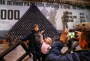 Visitors take pictures in front of a pyramid formed by German soldiers' World War Two helmets at the exhibition dedicated to the 75th anniversary since Leningrad siege was lifted, in Saint Petersburg