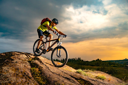 Cyclist Riding the Mountain Bike on Rocky Trail at Sunset. Extreme Sport and Enduro Biking Concept.