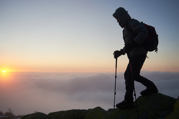 Tourist hiker in warm clothing with backpack and trekking poles climbing on rocky mountain peak on foggy cloudy landscape, misty blue sky and raising bright orange sun at dawn copy space background.