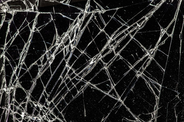 white cracked glass with dust on black background, texture