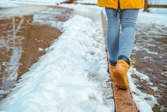 woman walking by city park passing puddles around. melting snow.