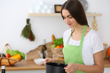 Beautiful Hispanic woman cooking soup in kitchen. Healthy meal and householding concepts