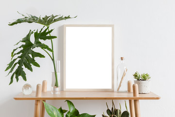 Scandinavian room interior with mock up photo frame on the brown bamboo shelf with beautiful plants, tropical leafs and accessories. White walls. Modern and floral concept of shelfs.