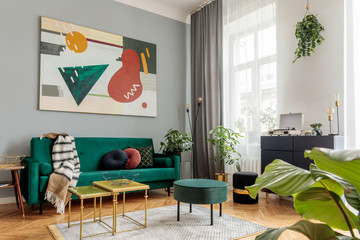 Luxury and modern home interior with design green sofa, commode, coffee tables, pouf and accessroies. A lot of plants in the room. Abstract painting. Stylish decor of living room with brown parquet.