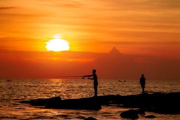 silhouette of fishermen on the beach