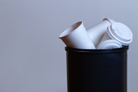 Garbage bin overflowing with paper, coffee cups. Coffee addiction and drinking a lot cups of coffee
