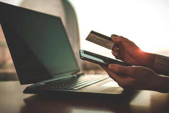 Using a laptop, credit card and mobile phone to buy and payment goods. Online shopping. Money transfer to people in need, charity, investment