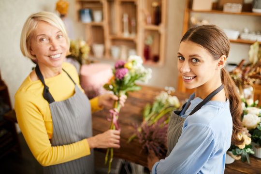High angle portrait of two female florists looking at camera and smiling while working in flower shop, copy space
