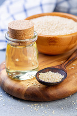 Organic sesame oil and sesame seeds in a wooden spoon.