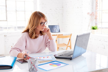Thinking businesswoman sitting in the office while working on laptop