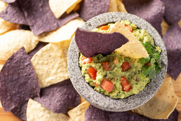 Granite Mulcajete filled with fresh guacamole surrounded by blue and yellow tortilla chips