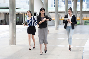 group of young business woman at rush hour walking in the street and watch the clock checking time to late on city streets