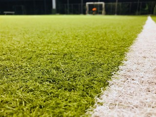 Close-up of Green artificial turf grass soccer football field And has a white stripe on the field as a field border