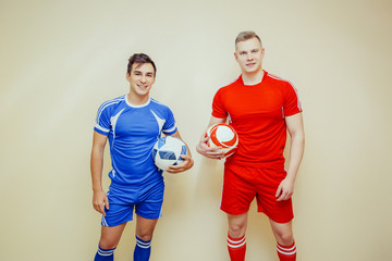 Two football players in blue and red uniform hold their balls and enjoy the great game