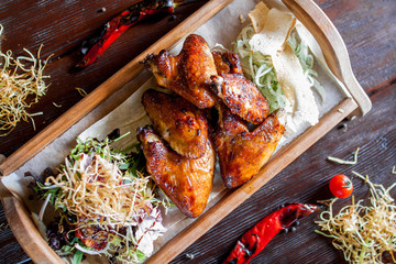 crispy chicken wings barbecue with peppers and tomatoes on a wooden tray
