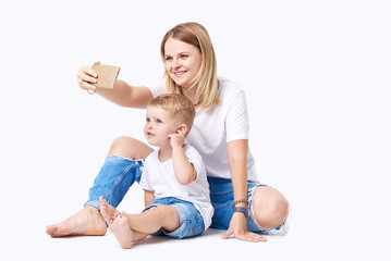 Happy mother laughing taking selfie with little son on smartphone, smiling single mom and cute adopted boy playing making photo posing for self portrait, mommy and kid watching video on cell