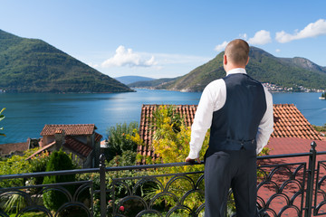 the groom in a suit standing on the terrace and looking at the sea