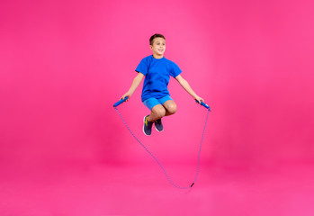 Full length portrait of boy jumping rope on color background