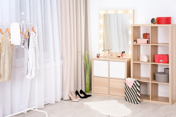 Dressing room interior with makeup mirror, wardrobe rack and shelving unit