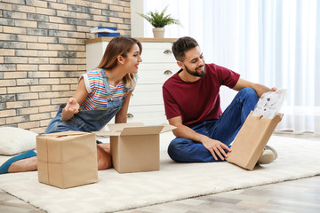 Young couple opening parcels on floor at home