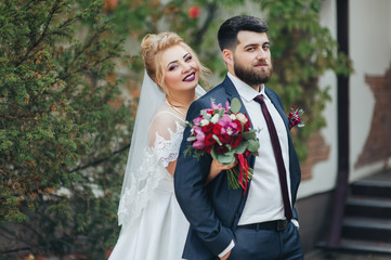 Bearded boyfriend in love and cute blonde bride hugging in a park on the nature. Portrait of lovers and smiling newlyweds in a green garden. Wedding photography in foliage.