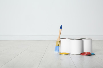 Cans of paint and brush on wooden floor indoors. Space for text