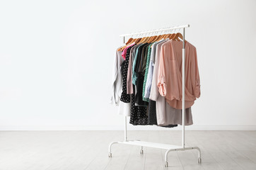 Wardrobe rack with stylish clothes near white wall indoors. Space for text Wall mural