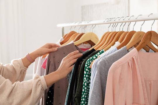 Woman choosing clothes from wardrobe rack, closeup
