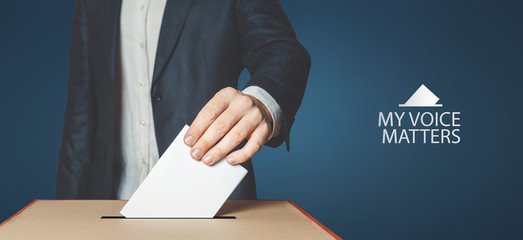 My voice matters concept. Man voter holds hand a ballot above the ballot box