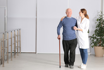 Elderly man with female caregiver indoors. Space for text