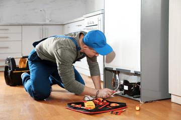 Obraz Male technician in uniform repairing refrigerator indoors - fototapety do salonu