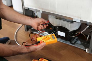 Obraz Male technician repairing broken refrigerator indoors, closeup - fototapety do salonu